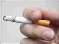 A cigarette is held between two fingers