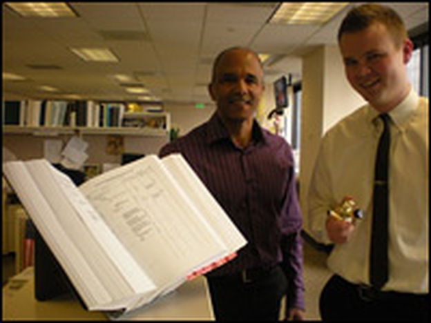 Bret Ewing (right) and Jim Henderson, import specialists in Seattle, stand with the <em>Harmonized Tariff Schedule Of The United States.</em>