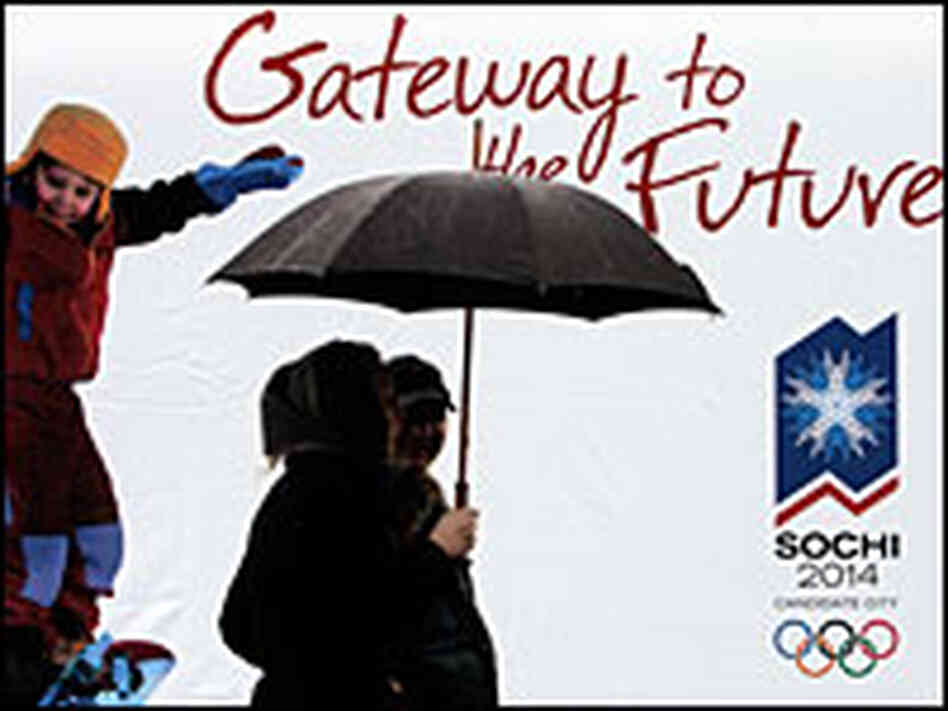 A couple walks in front of a poster for the 2014 Winter Olympics in Sochi, Russia.