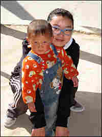 Bai Yitong plays with a fellow villager outside her office
