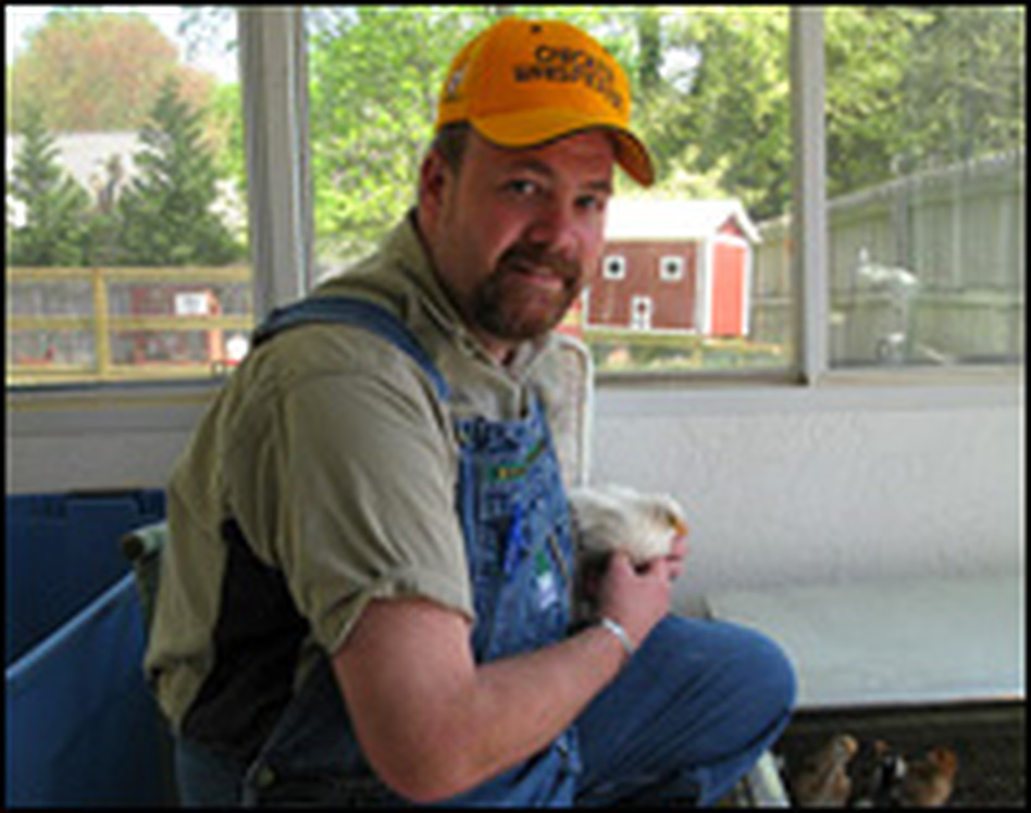 """Andy Schneider is known as Atlanta's """"Chicken Whisperer.""""  He has several kinds of chicken coops in his backyard, including a 4-by-6 chicken tractor on wheels that urban farmers can move around in their yards."""