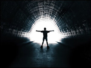 Person in a tunnel walking toward light.