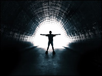 Person in a tunnel walking toward light.