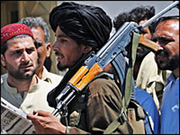 An armed Pakistani Taliban chats with residents in the Buner district of Pakistan's troubled Swat Valley on April 23. The militants launched an attack on the district, which is about 60 miles outside Islamabad, the Pakistani capital, in early April.