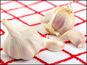 A garlic bulb and cloves of garlic on a red