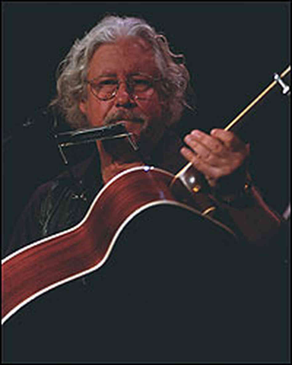 Arlo Guthrie, with guitar.