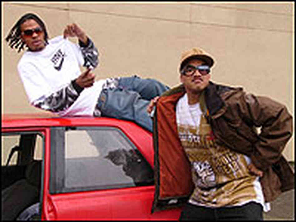 Two young men goof around on a battered red car, one wearing a Hyphy T-shirt.