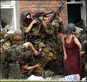 A Russian soldier carries an injured colleague as other soldiers and women take cover.