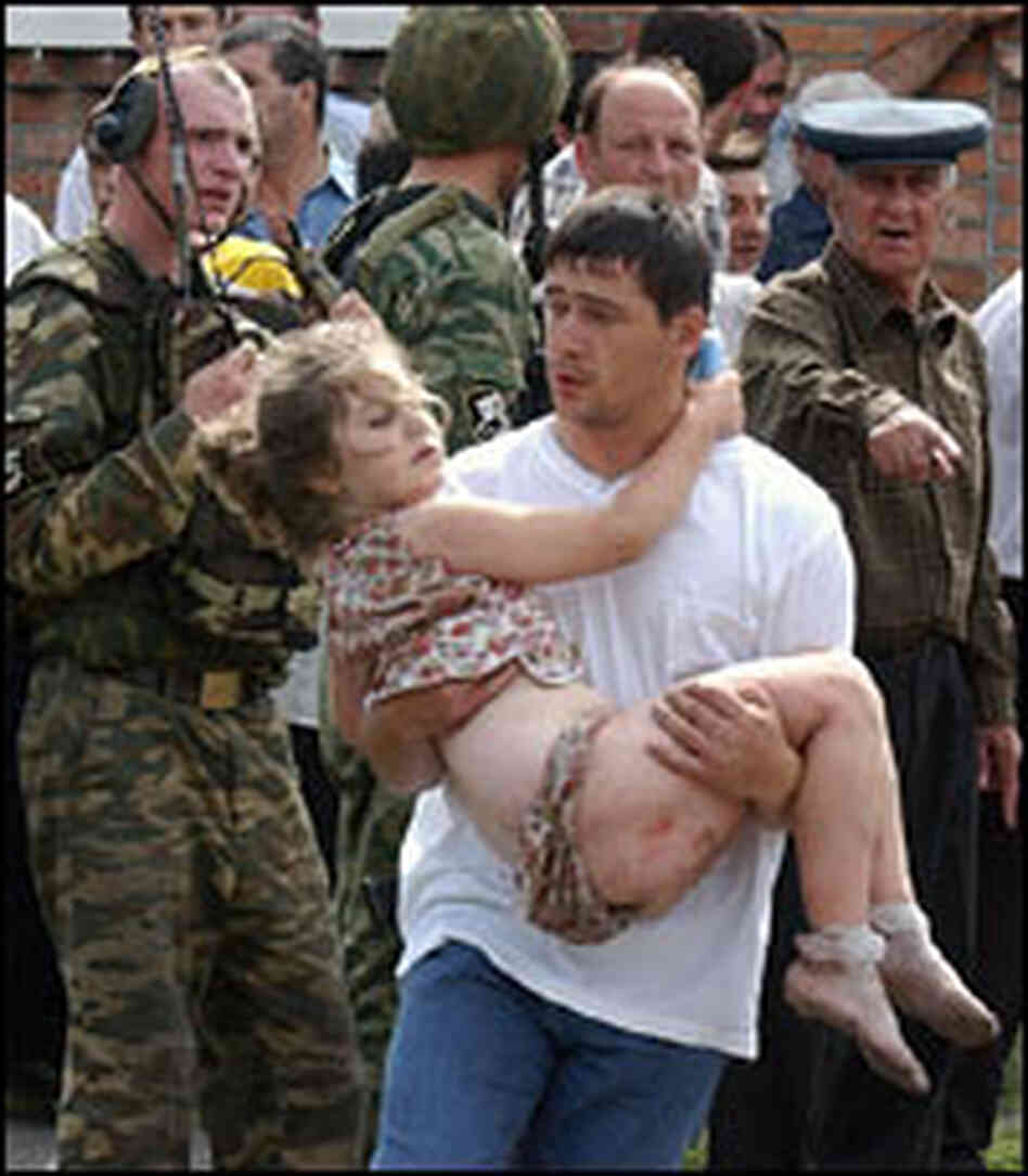An Ossetian man carries a girl during a rescue operation at the Beslan School No. 1.