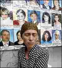 A woman cries in the Beslan school gymnasium where siege victims' photos hang on the wall.