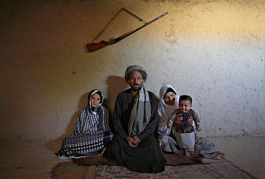 Majabin Mohammed, 13, at left, sits with her husband of six months, Mohammed Fazal, 45, his first wife and their child. Village elders advised him to accept Majabin as payment for a gambling debt.