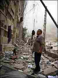 A resident of Beirut's southern suburbs, a Hezbollah stronghold, check damage after Israeli bombing