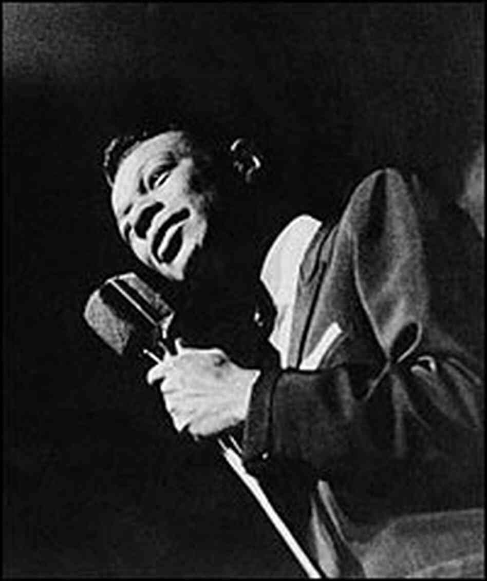 Nat 'King' Cole performs to an audience in the 1950s.