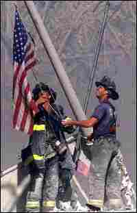 Firefighters raise the flag at Ground Zero