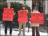 Three people stand with signs outside Egyptian embassy in Washington, D.C.