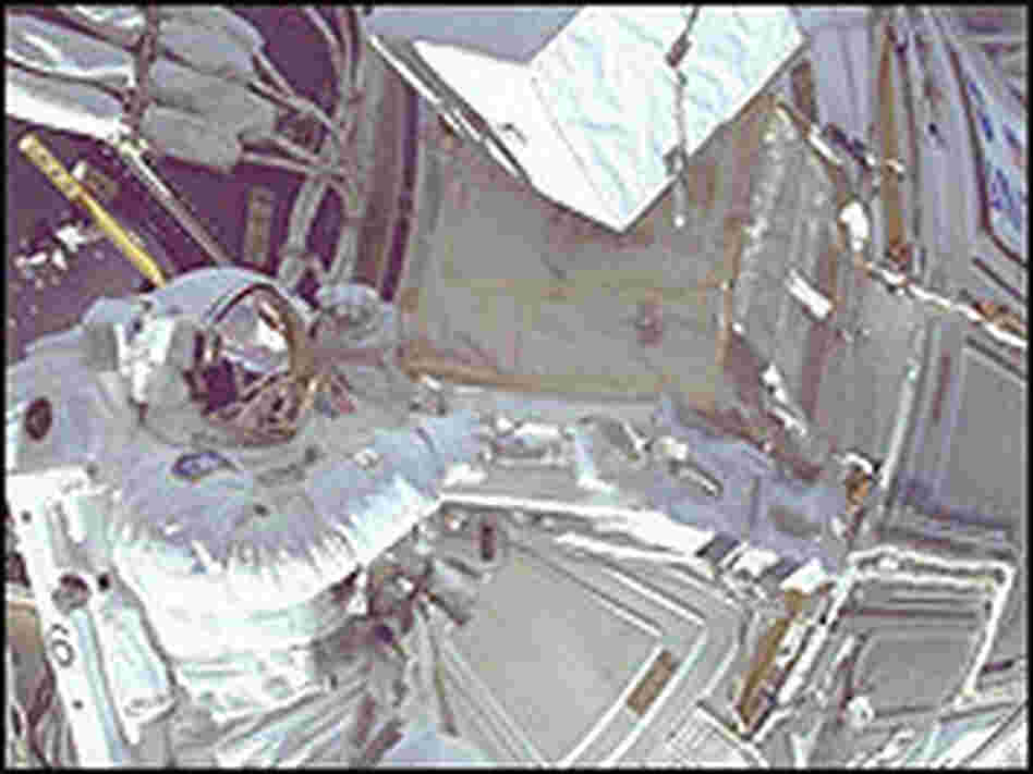 Astronaut Daniel Barry works on the International Space Station during a space walk in 1999.