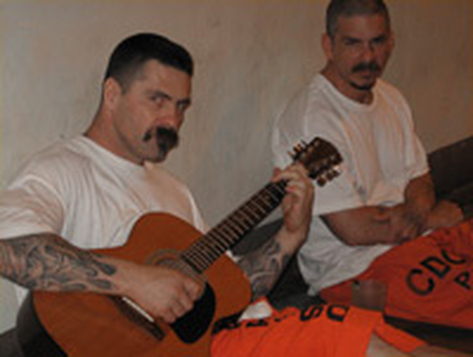 Two inmates in San Quentin's gymnasium pass the time with a guitar. There are no programs or activities. Except for two meals in the cafeteria, most inmates spend all day, every day locked in the gym.