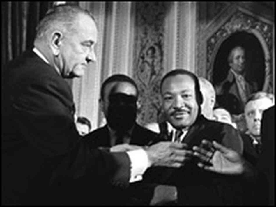 President Lyndon B. Johnson greets visitors as Rev. Martin Luther King, Jr., looks on.