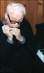 Toots Thielemans at piano, playing a harmonica. Photo by Dimitri Tolstoi