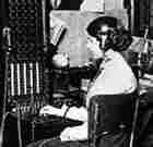 An old-fashioned switchboard operator with headphones and a series of plugs to connect calls.