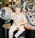 Mike Coup sits among the old equipment and the fans museum in Andover, Kansas
