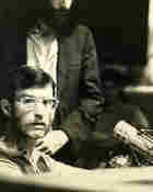 Ken Sleeman, the manager of WGTB-FM in the 1970s, seated at a microphone.