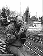 Don Hunter recording sound at an old train depot, with abandoned train cars in the background.