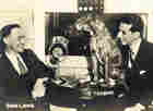 Don Lang and Robert Trout site at a table with a microphone and the metal dog, Toughie.