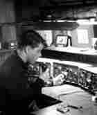 Jonathan Kern at age 15, sitting in a room filled with radio equipment and holding a microphone.