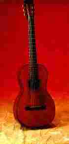 Mark Twain's guitar, a Martin, style 2½-17, stands upright. It is a rich, deep red color