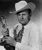 Bill Monroe, guitar in hand, wearing a cowboy hat.