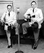 The Stanley Brothers holding their guitars, standing in front of a microphone