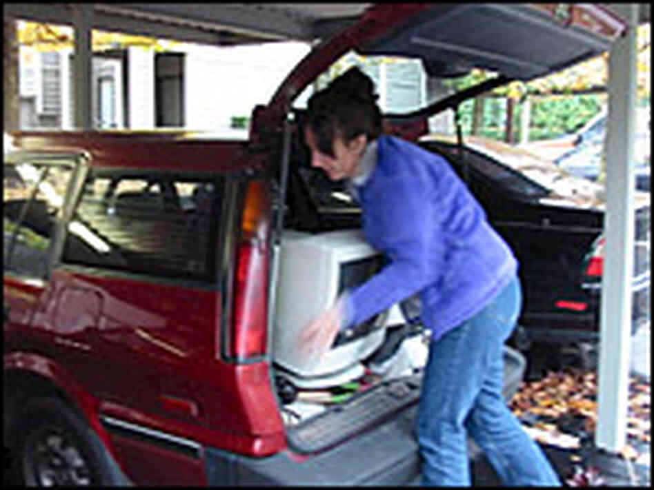 Joanna Slaybaugh packs her computer into her station wagon on moving day.