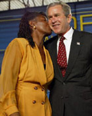 President Bush receives a kiss from a woman who recently moved off welfare