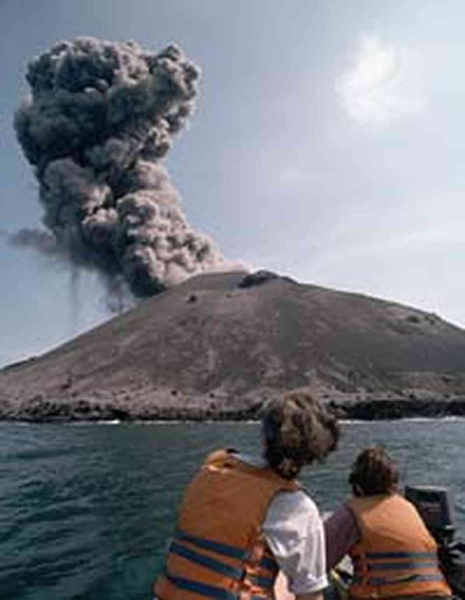 Tourists watch as smoke billows from a minor eruption of Anak Krakatau in 1995.