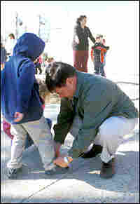 Principal Mark Cumella ties a child's shoe. Credit: Steve Drummond, NPR.