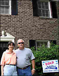 Angela and Julian Timmons stand in front of the home they won at auction.