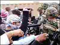 National Guardsmen practice crowd control in a mock Iraqi village during training exercises