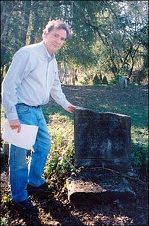 John Boatwright stands near broken headstone.