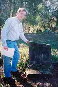 John Boatwright stands near broken headstone.