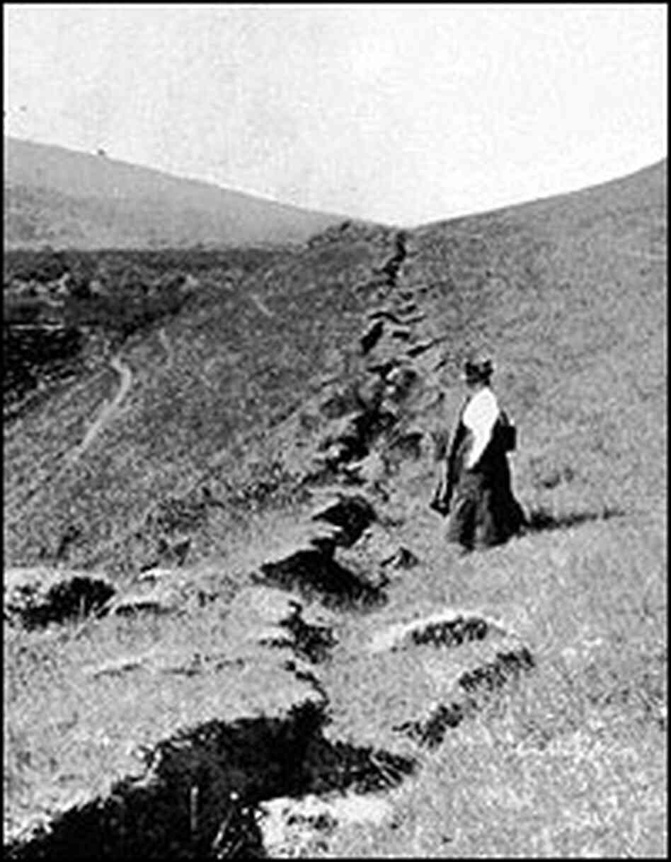A woman stands near the 1906 ground rupture.