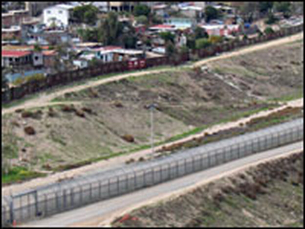 An overhead view of the double- and triple-fencing used in the 14-mile-long border fence separating San Diego and Tijuana. In the enlarged image, a Tijuana neighborhood is visible at left. The open field at right is in California.