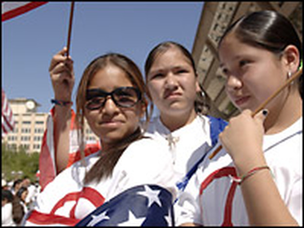 Middle school students Maria Mancera, Cindy Roque and Magaly Mancera hold U.S. flags as they watch protesters at the Mega March on City Hall in Dallas on Sunday.