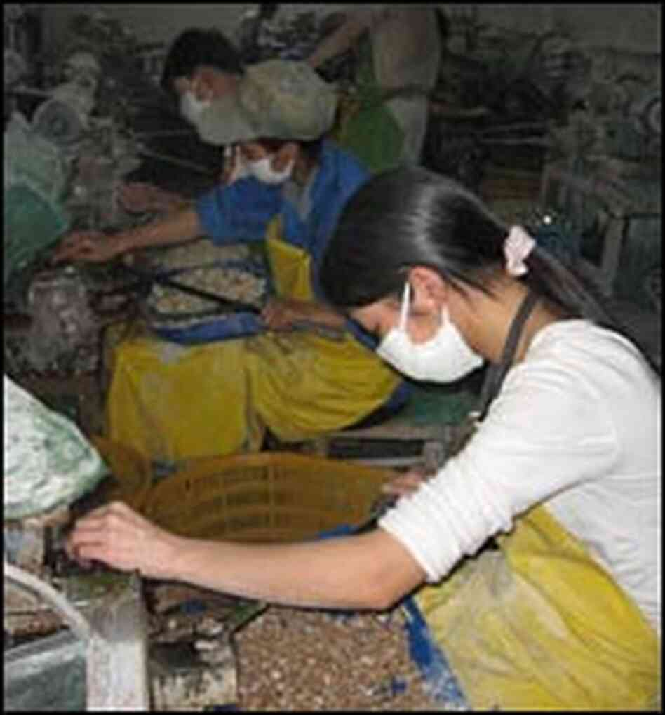 Workers buff baskets of buttons at a factory