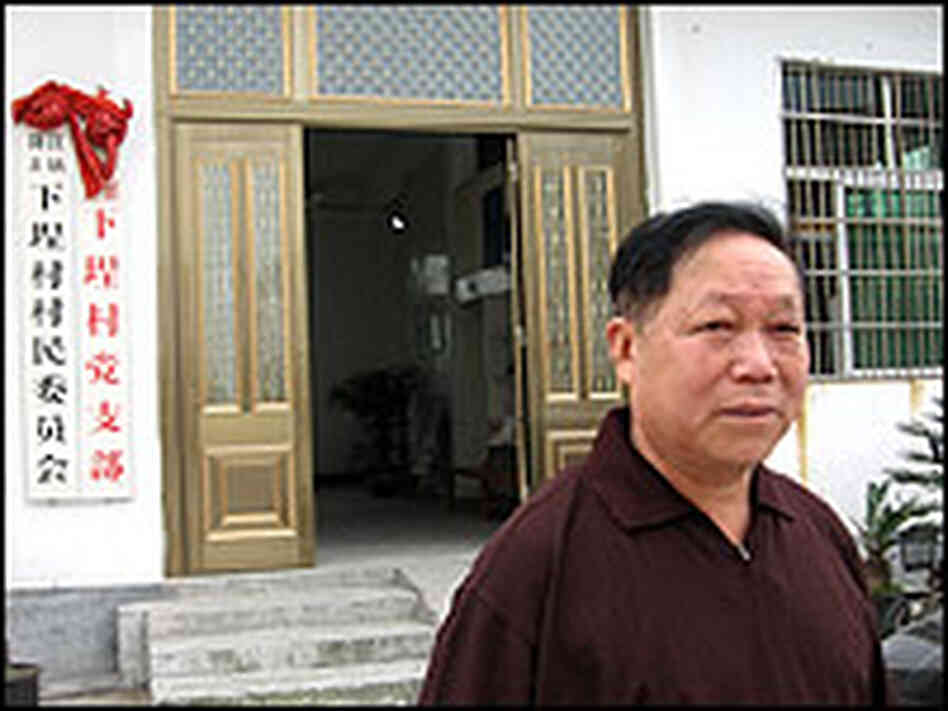 Wu Houhui stands in front of the local Communist Party building.