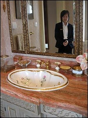 Saleswoman Karen He shows a wash basin  decorated with 24-carat gold.