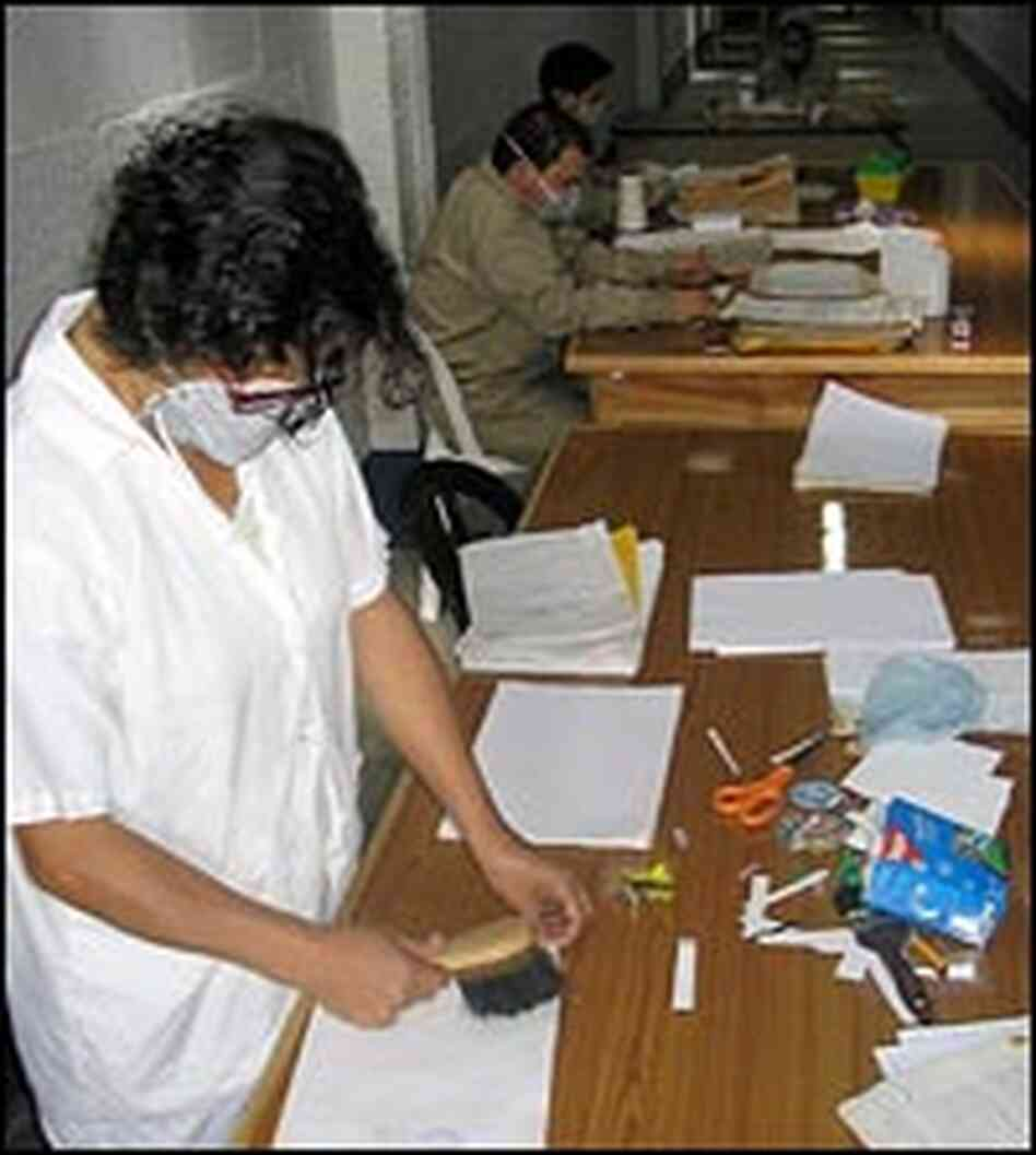 Workers clean documents in the Police Archive.