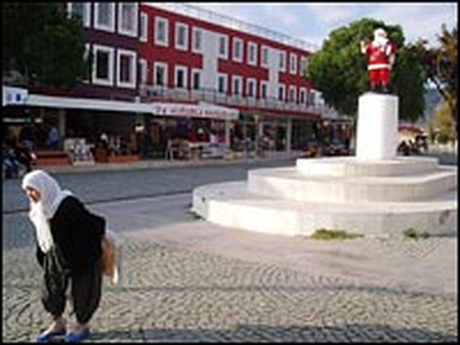 A Turkish woman passes in front of a controversial statue of Santa Claus, called Noel Baba in Turkish, in the town square of Demre. Last year, Russian diplomats criticized local Turkish officials, who replaced a bronze statue of a haloed Saint Nicholas, holding a Bible, with this more secular symbol of Christmas.