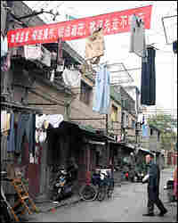 Red banners, encouraging residents to move out as soon as possible, festoon the neighborhood.