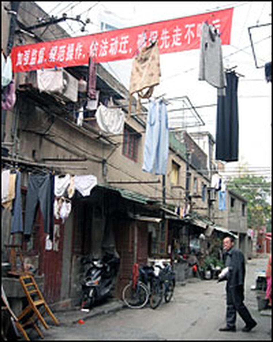 Red banners encouraging residents to move out as soon as possible festoon the alleys.